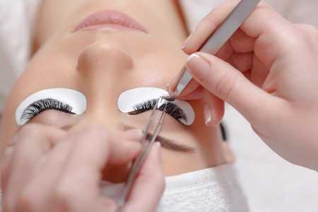 Photo pour Permanent makeup. Eyelash Extension Procedure. Woman Eye with Long Eyelashes. Professional stylist lengthening female lashes. Eyelash extension procedure - master and a client in a beauty salon - image libre de droit