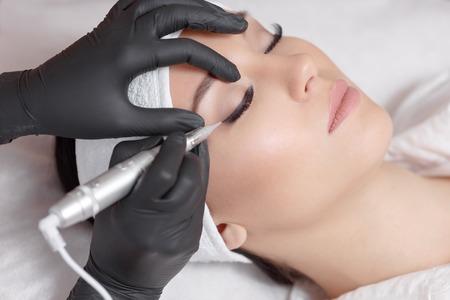 Foto de Cosmetologist making permanent makeup, close up. Tattooist making permanent make-up. Attractive lady getting facial care and tattoo. Permanent make-up tattoo at beauty salon - Imagen libre de derechos