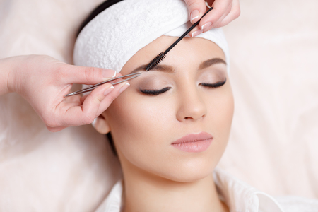 Photo pour Permanent makeup. Beautiful young woman gets eyebrow correction procedure. Young woman tweezing her eyebrows in beauty saloon. Young woman plucking eyebrows with tweezers close up - image libre de droit