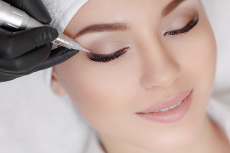 Photo pour Cosmetologist making permanent make up at beauty salon - image libre de droit