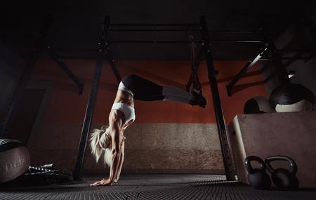 Foto de Fitness woman workout on the TRX in the gym - Imagen libre de derechos