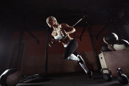 Photo for Fitness woman workout on the TRX in the gym - Royalty Free Image