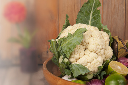 Fresh cauliflower and vegetables in old pan