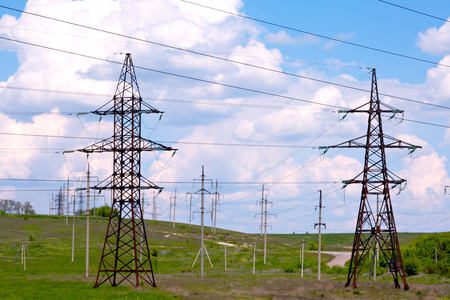 Photo pour High voltage power line on a green field with blue sky and clouds - image libre de droit