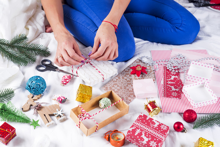 Photo for Girl in a cozy knit sweater decorated with a Christmas gift box - Royalty Free Image