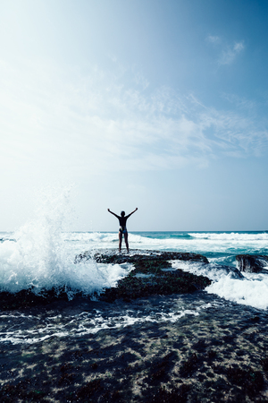 Cheering woman outstretched arms at seaside mossy coral reef