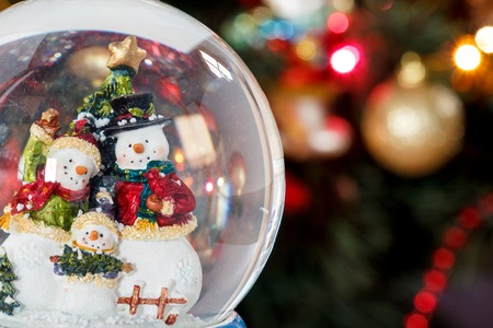 Photo for Snow globe with happy snowman family on christmas tree blured background - Royalty Free Image