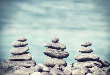 Photo pour Vintage retro hipster style image of stones on beach, Zen spa concept background. - image libre de droit
