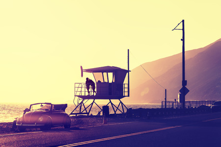 Photo pour Vintage filtered sunset over beach with lifeguard tower, Pacific Coast Highway, USA. - image libre de droit