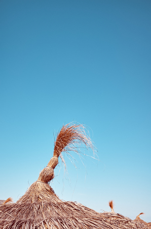 Foto de Retro toned close up picture of thatched umbrella on a beach. - Imagen libre de derechos
