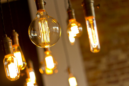 Foto de Decorative antique edison style light bulbs against brick wall background - Imagen libre de derechos