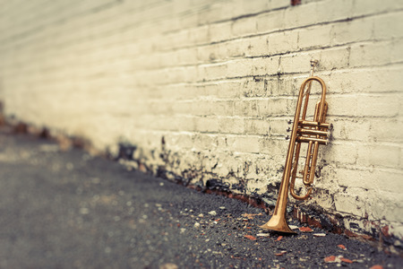 Foto de Old worn trumpet stands alone against a grungy pealing white brick wall outside a jazz club - Imagen libre de derechos