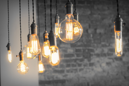 Photo pour Decorative antique edison style filament light bulbs against brick wall - image libre de droit