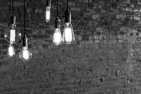 Photo pour Decorative antique edison style light bulbs against brick wall background - image libre de droit