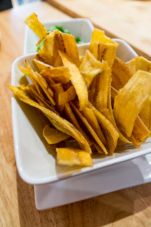Photo for Crispy fried plantain chips with fresh spicy guacamole - Royalty Free Image