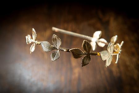 Photo for Golden laurel leaf Greek or Roman crown on dark moody wooden table - Royalty Free Image