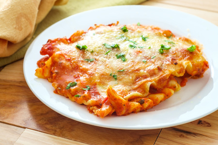 Photo pour Home made Italian baked cheese lasagna on wooden kitchen table - image libre de droit
