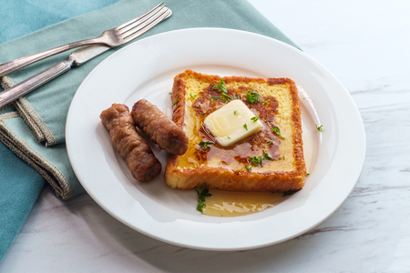 Photo for Classic American breakfast french toast with maple syrup served with side of sausage links - Royalty Free Image