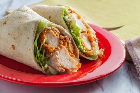 Photo for Crispy chicken Caesar salad wrap sandwich with romaine lettuce - Royalty Free Image