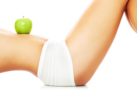 Photo for A picture of a woman holding a green apple on her fit belly - Royalty Free Image