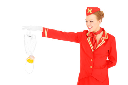 Foto de A picture of an attractive stewardess presenting an oxygen mask over white background - Imagen libre de derechos