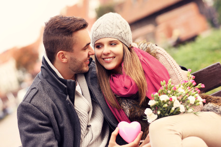 Photo pour A picture of a couple on Valentine's Day in the park with flowers and heart - image libre de droit