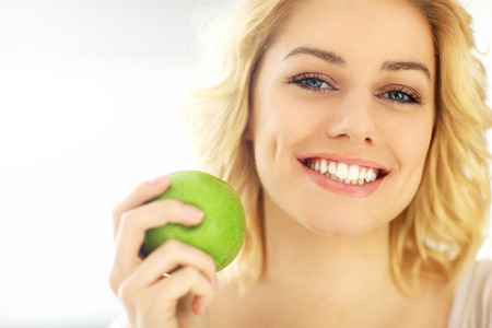Foto per A picture of a young woman eating an apple at home - Immagine Royalty Free
