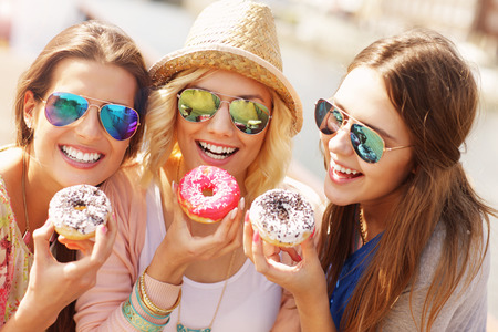 Photo for Group of friends eating donuts in the city - Royalty Free Image