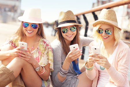 Foto de A picture of group of friends using smartphones in the city - Imagen libre de derechos