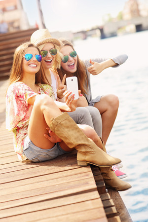 Photo pour A picture of group of friends taking selfie in the city - image libre de droit