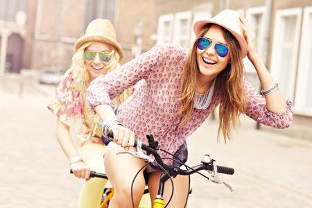 Foto de A picture of two girl friends riding a tandem bicycle in the city - Imagen libre de derechos