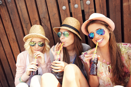 Photo pour A picture of a group of girl friends drinking soda on the pier - image libre de droit