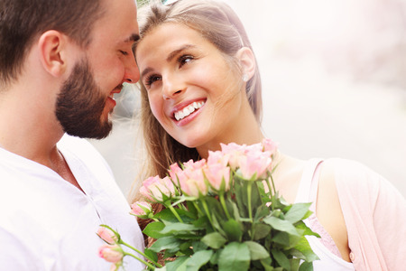 Photo for A picture of a young romantic couple with flowers in the city - Royalty Free Image