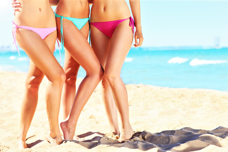 Photo for  female legs in bikini on the beach - Royalty Free Image