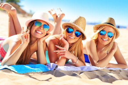 Photo for A picture of a group of friends sunbathing on the beach - Royalty Free Image