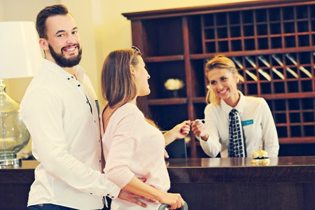 Foto de Picture of couple and receptionist at counter in hotel - Imagen libre de derechos