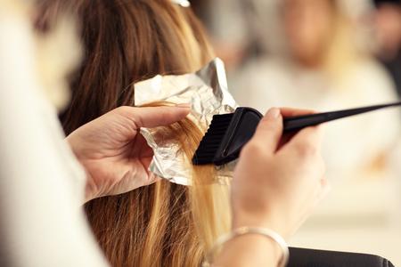 Foto de Picture showing hairdresser coloring hair in studio - Imagen libre de derechos