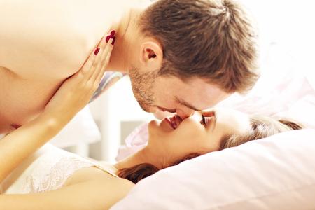 Foto de Picture of young couple kissing in bed - Imagen libre de derechos