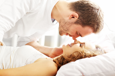Photo for Picture of young couple kissing in bed - Royalty Free Image