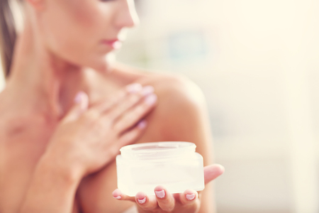 Photo pour Picture of a fit woman holding lotion over her body - image libre de droit