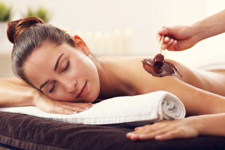 Photo for Beautiful woman getting chocolate massage in spa - Royalty Free Image