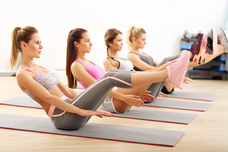 Photo for Young women doing sit-ups in a gym - Royalty Free Image