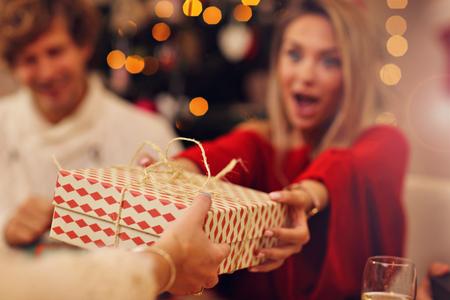 Photo pour Group of friends giving Christmas presents at home - image libre de droit
