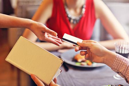 Foto de Picture showing people paying in restaurant by credit card reader - Imagen libre de derechos