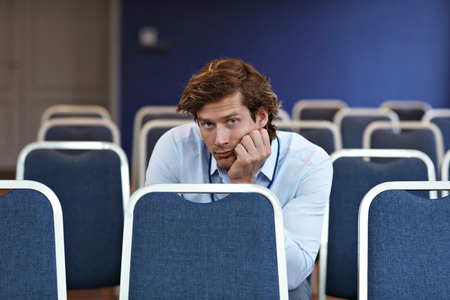 Photo pour Young man sitting alone in conference room - image libre de droit