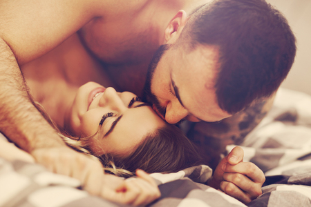 Photo for Sexy young lovers being intimate in bed - Royalty Free Image
