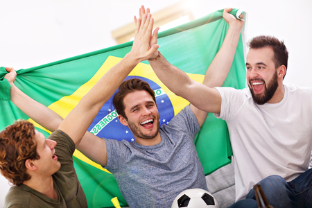 Photo pour Happy male friends cheering and watching sports on tv - image libre de droit