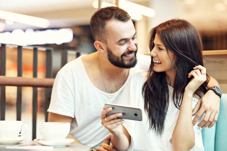 Foto de Romantic couple dating in cafe and using smartphone - Imagen libre de derechos
