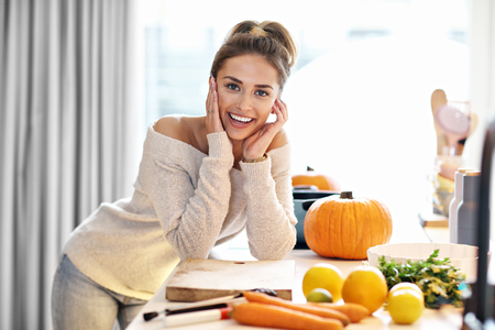 Photo for Adult woman in the kitchen preparing pumpkin dishes for Halloween - Royalty Free Image