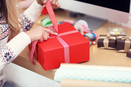 Foto de Adult woman at home wrapping Christmas presents - Imagen libre de derechos